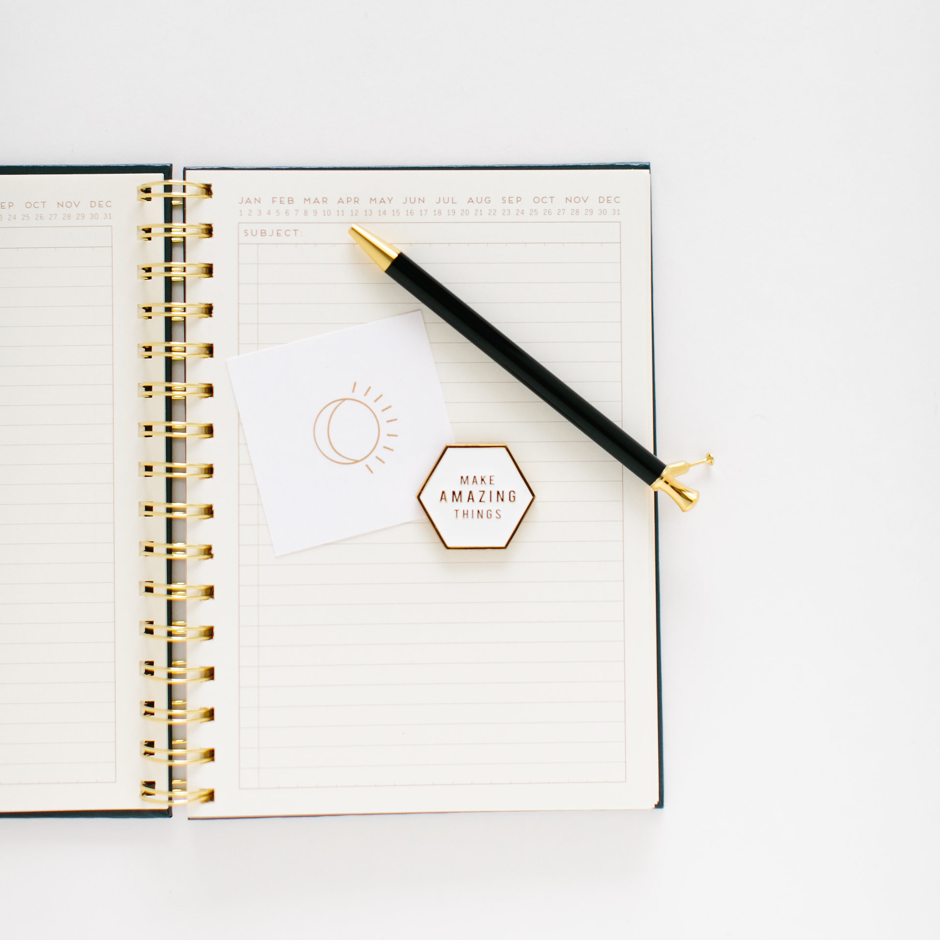 Open journal with pen and badge saying Make Amazing Things