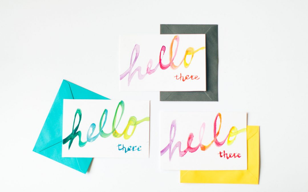 Three coloured envelopes, blue, yellow and dark grey with postcards on top saying Hello there to illustrate email marketing